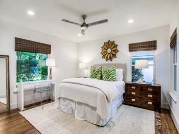 Master bedroom with ceiling fan and refinished floors