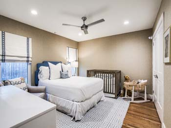 A bright new bedroom with beautiful wood flooring and custom paint
